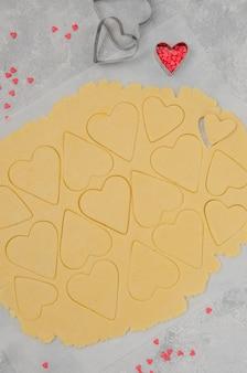 Strato di pasta frolla con cuori tagliati per san valentino.