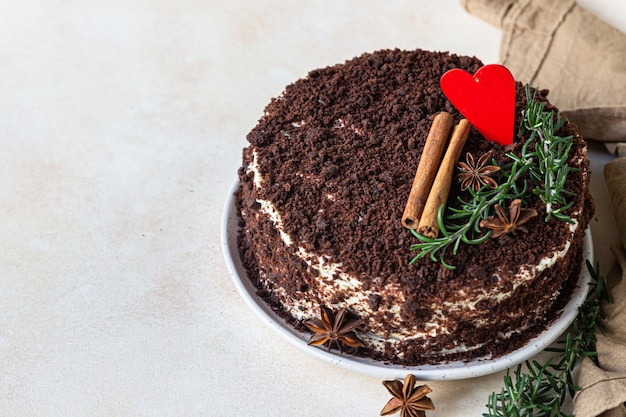 Torta al cioccolato a strati decorata con cuore, rosmarino, cannella e anice
