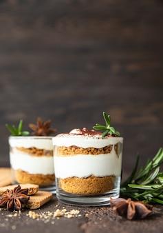 Dessert a strati in vasetto di vetro con crumble di biscotti e panna montata decorato con rosmarino e anice, superficie marrone scuro