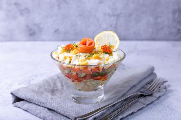 Insalata a strati con trota salata, caviale, uova e verdure