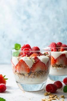 Yogurt a strati, muesli e frutta, fragola e lampone. cibo sano per la colazione