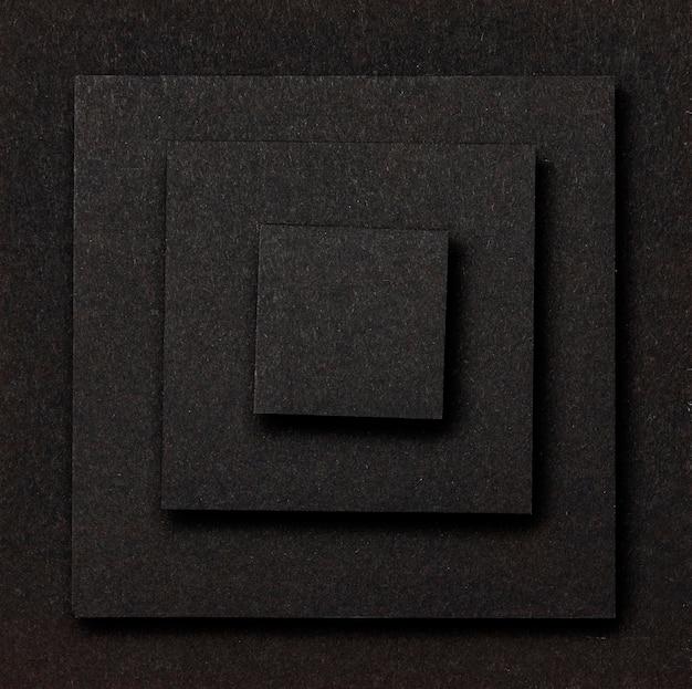 Strati di quadrati neri sfondo piatto laici