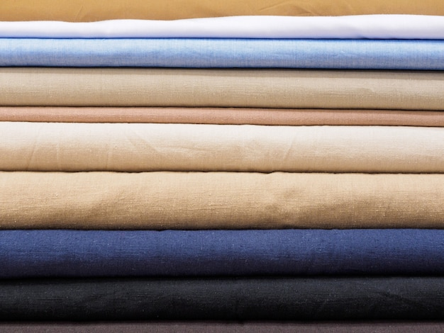 Strati di tessuto naturale bello in colori pastello in un negozio o in una fabbrica, primo piano.