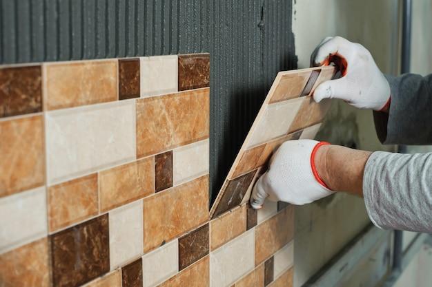 Posa di piastrelle in ceramica. piastrellista che posiziona la piastrella di ceramica in posizione sopra l'adesivo