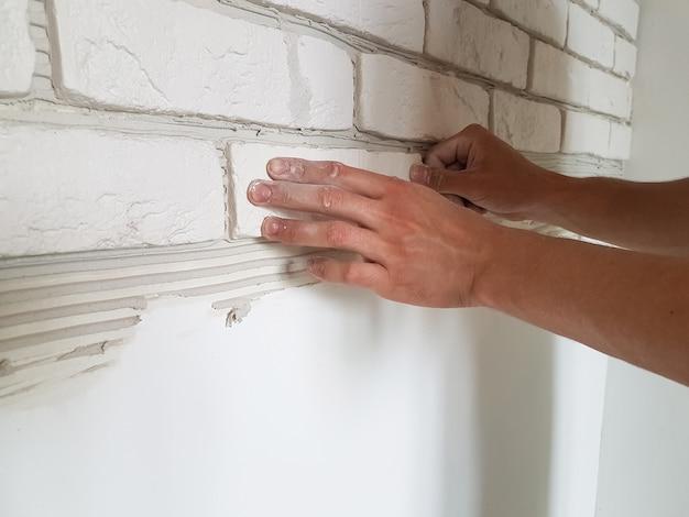 Posa di piastrelle di gesso in file sul muro con mani maschili. riparazione a casa.