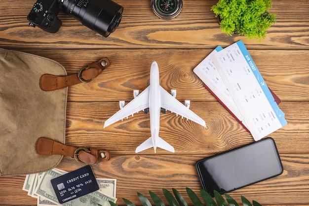 Layout di accessori da viaggio in aereo su uno sfondo di legno