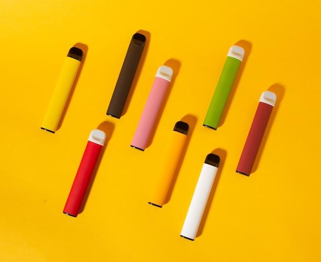 Disposizione delle sigarette elettroniche usa e getta colorate con le ombre