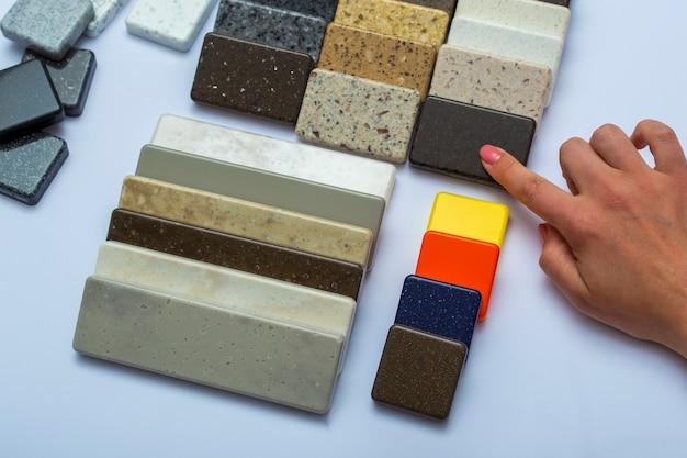 Layout di pietre naturali vista dall'alto, primo piano. la mano della donna pubblicizza il materiale di riparazione. piastrelle per pavimenti, piastrelle, controsoffitti.