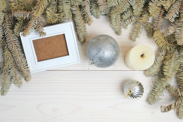 Layout di una cornice per foto, carta, matita su un tema natalizio su una superficie di legno bianca