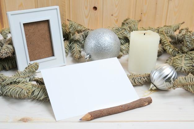 Layout di una cornice per foto, carta, matita su un tema natalizio su un tavolo di legno bianco
