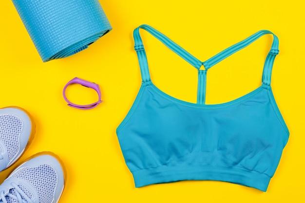Disposizione dei vestiti e degli accessori di sport sulla tavola gialla