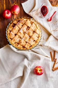 Disposizione o natura morta con la torta di mele fatta domestica nella forma per la cottura sulla tavola coperta di tovaglia leggera sulla cucina a casa. vista dall'alto con spazio di copia