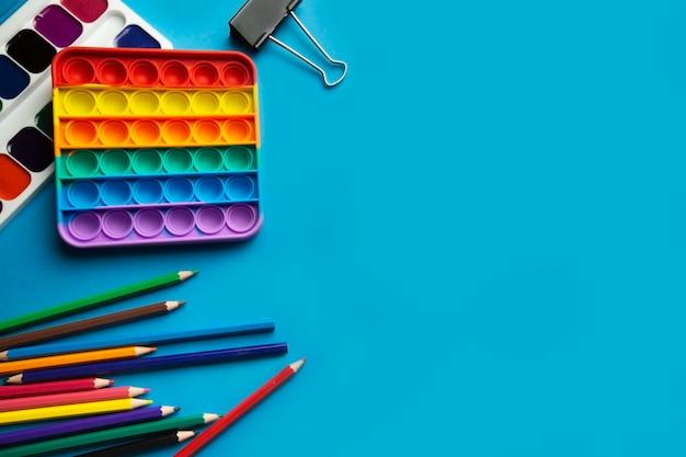 Layout vista dall'alto di oggetti scolastici per bambini pop it toy acquerelli matite colorate