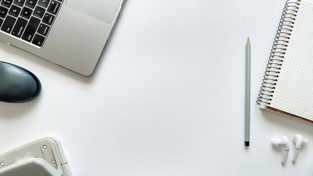 Layout sul tema dell'istruzione o lavoro su uno sfondo bianco con blocco note, penna, laptop, mouse del computer, cartella per documenti, perforatrice, cuffie, matite. disposizione piatta, vista dall'alto