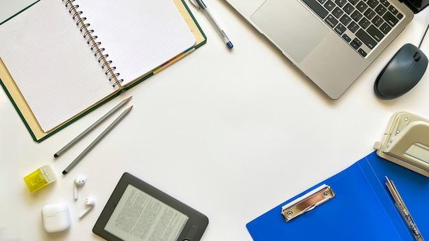 Layout sul tema dell'istruzione o lavoro su uno sfondo bianco con blocco note, penna, laptop, mouse del computer, cartella per documenti, perforatrice, cuffie, matite. disposizione piana, vista dall'alto.