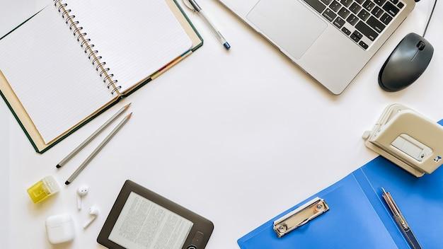 Layout sul tema del processo di lavoro o dell'istruzione su uno sfondo bianco con blocco note, penna, laptop, mouse del computer, tablet, perforatore, cuffie, matite. disposizione piana, vista dall'alto.