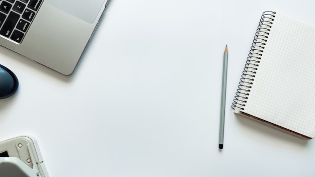 Layout sul tema del processo di lavoro o dell'istruzione su uno sfondo bianco con un computer portatile con penna per blocco note