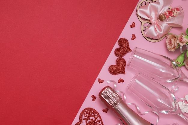 Disposizione due cuori rossi, bicchieri, champagne, fiori su uno sfondo rosa-rosso con il concetto di data o festa di san valentino dello spazio della copia