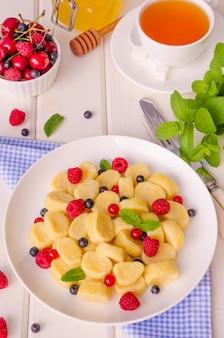 Gnocchi pigri di ricotta con frutti di bosco freschi, foglie di menta, panna acida e miele.