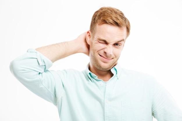 Pigro bel giovane uomo d'affari in piedi e grattandosi la testa sul muro bianco