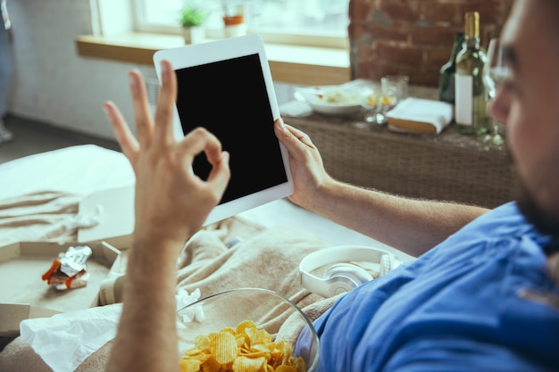 Uomo pigro che vive nel suo letto circondato da un disordine che usa gadget guardando film