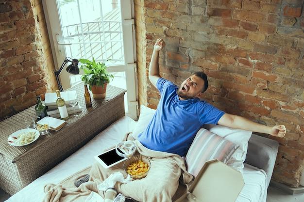 Uomo pigro che vive nel suo letto circondato da disordine