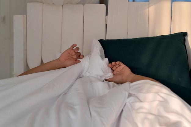 Uomo pigro che dorme a letto sotto una coperta bianca al mattino, non voglio svegliarmi, vacanza, relax