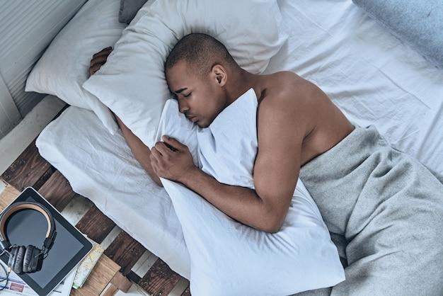 Mattinata pigra. vista dall'alto del giovane africano che dorme sdraiato nel letto di casa