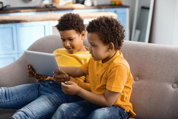 Passatempo pigro. simpatici ragazzini seduti sul divano e guardando insieme un cartone animato sul tablet, godendosi il loro tempo libero