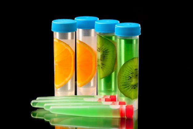 Tubi lb archiviati con liquido o con parti di frutta su sfondo nero.