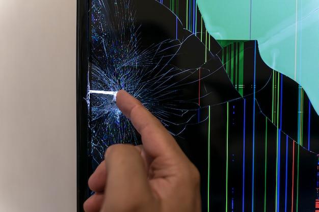 Lo schermo del monitor lcd è rotto. la mano di un uomo tocca una crepa.