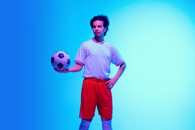 Capo. giocatore di calcio o di calcio sulla parete dello studio blu sfumato alla luce al neon - posa sicura con la palla. copyspace.