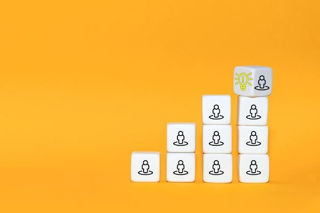 Leader con idea e innovazione. il cubo si capovolge con l'icona della lampadina e il simbolo umano.