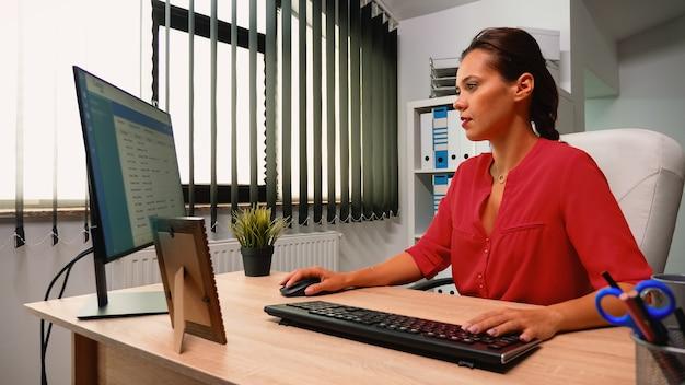 Leader che scrive sul computer seduto da solo nella moderna stanza dell'ufficio. imprenditore ispanico che viene al lavoro, nell'area di lavoro dell'azienda professionale digitando sulla tastiera del computer guardando il desktop