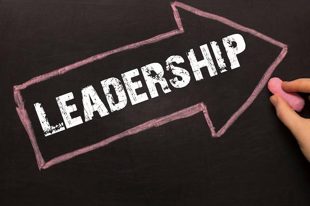Leadership - lavagna con freccia su sfondo nero