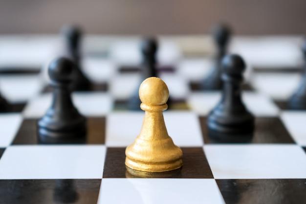 La principale pedina d'oro principale sta davanti alle normali pedine nel gioco degli scacchi