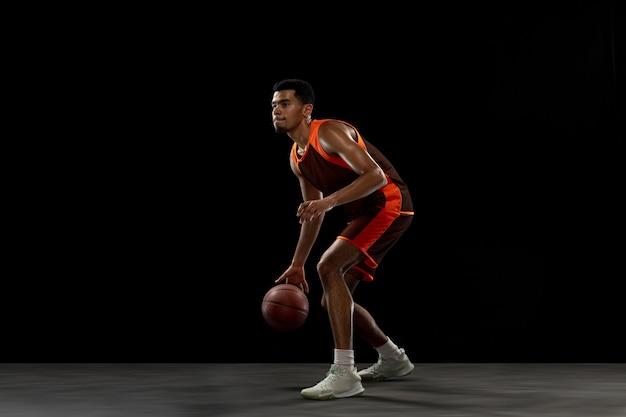 Primo. giovane propositivo giocatore di basket afro-americano che si allena, pratica in azione, movimento isolato su sfondo nero. concetto di sport, movimento, energia e stile di vita dinamico e sano.
