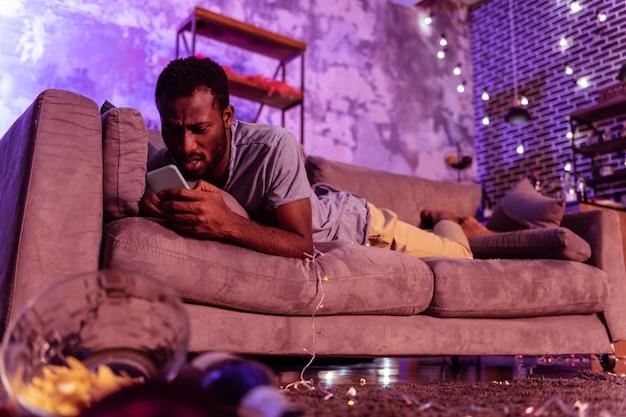 Appoggiandosi al cuscino. uomo barbuto spiacevole che invia messaggi di testo sullo smartphone mentre giaceva nella sporcizia e negli avanzi