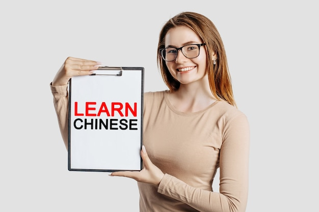 Impara cinese. bella giovane donna d'affari con gli occhiali tiene una lavagna per appunti con spazio simulato isolato su sfondo grigio