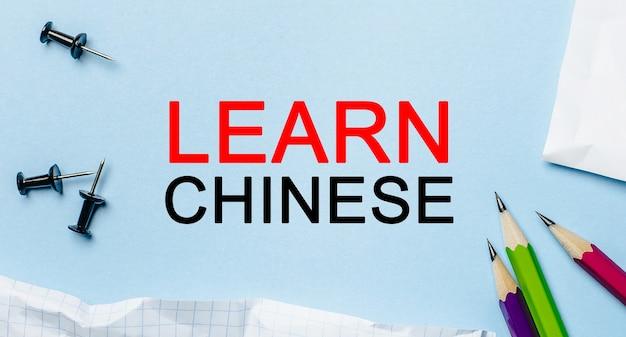 Impara il cinese su un blocco note bianco con le matite su uno spazio blu