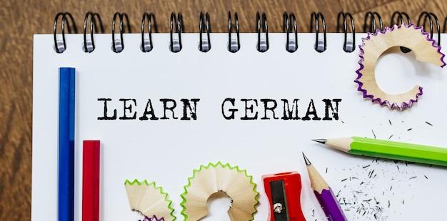 Impara il testo tedesco scritto su una carta con le matite in ufficio Foto Premium