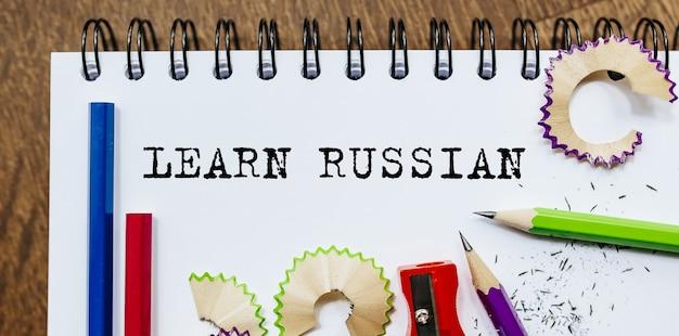 Impara il testo russo scritto su una carta con le matite in ufficio
