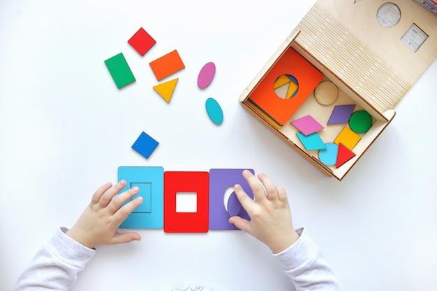 Imparare colori e forme. il bambino raccoglie un selezionatore. giocattoli di logica educativa per bambini. primo piano delle mani dei bambini. giochi montessori