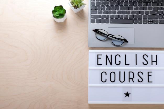 Concetto di apprendimento. corso di inglese. laptop, occhiali per computer su una parete in legno, vista dall'alto, copia dello spazio.
