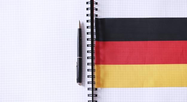 Imparare le lingue straniere. blocco note per le voci e una bandiera. corsi di lingua, audizione audio.