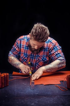 Leather artist lavora con articoli in pelle nel suo negozio di concia