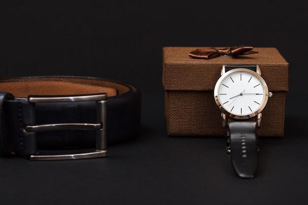 Cintura in pelle con fibbia in metallo, orologio con cinturino in pelle nera e confezione regalo marrone su sfondo nero. accessori per uomo.
