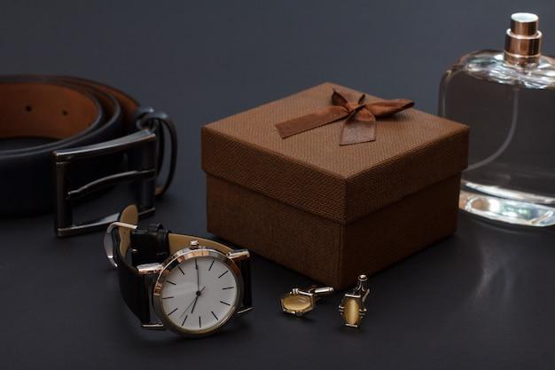 Cintura in pelle con fibbia in metallo, orologio con cinturino in pelle nera, confezione regalo marrone, gemelli e colonia da uomo su sfondo nero. accessori per uomo.