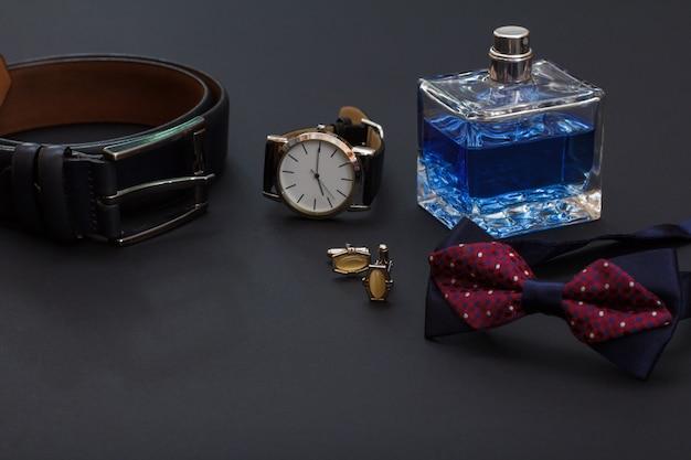 Cintura in pelle con fibbia in metallo, orologio con cinturino in pelle nera, colonia da uomo, gemelli e papillon su sfondo nero. accessori per uomo.
