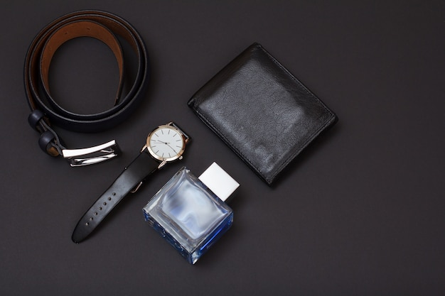 Cintura in pelle con fibbia in metallo, orologio con cinturino in pelle nera, colonia da uomo e borsa su sfondo nero. accessori per uomo. vista dall'alto.